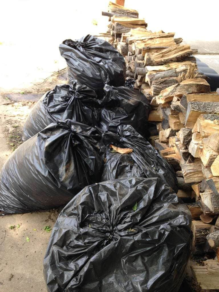 Bags of Gathered Leaves by Wood Pile for Compost